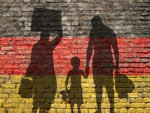 Flüchtlinge vor Mauer in den Farben Schwarz Rot Gold; Quelle: Jonathan Stutz / fotolia.com, Fotolia_91458861